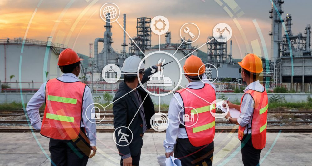 The engineer discussing a new project with large industry background with industrial instruments in the factory and cyber and physical system icons.